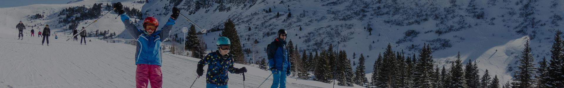 dzieci zjeżdżające na nartach